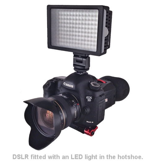 a dslr camera with an led light in the hotshoe.